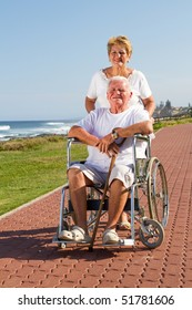 happy senior wife push husband on wheelchair at beach