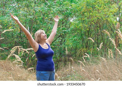 Happy senior woman arms up and breathing deep outdoors with nature in the park background. Freedom concept, summer outdoors, energy of nature, power of a woman