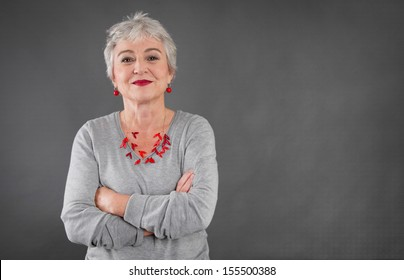 Happy senior woman with arms crossed over grey background isolated.