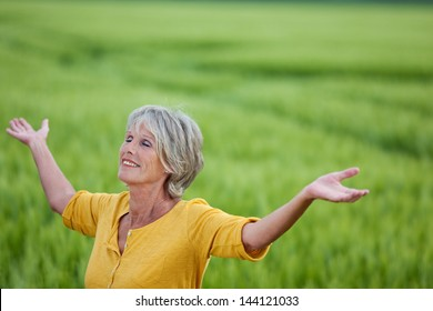 Happy senior woman with arms outstretched enjoying nature on grassy field