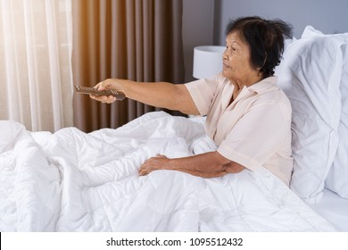 happy senior woman in bed with remote control and watching tv