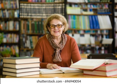 Happy senior woman with books in library