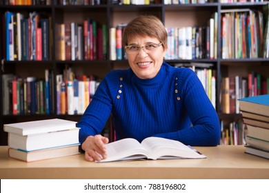 Happy senior woman  with books in library.