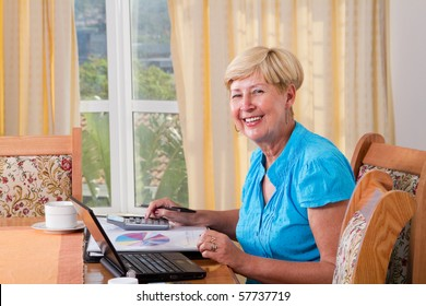 happy senior woman calculating her finance at home
