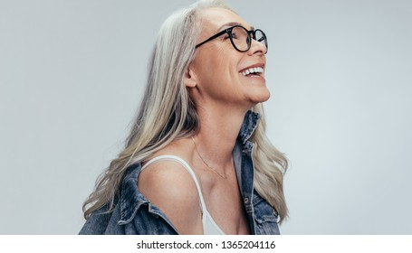 Happy senior woman in casuals looking away and smiling over grey background. Cheerful mature woman in denim shirt and eyeglasses.