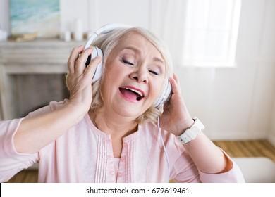 Happy senior woman with closed eyes wearing headphones and singing