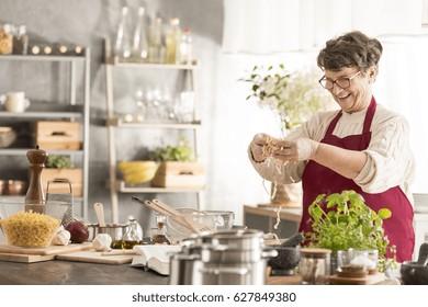 Happy senior woman cooking in her modern kitchen