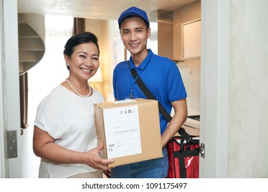 Happy senior woman and courier holding big box