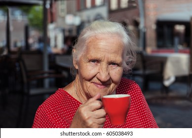 Happy senior woman with cup of coffee outdoor. Selective focus