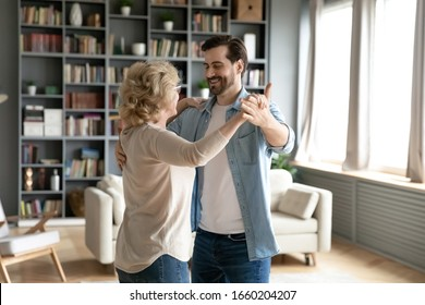 Happy senior woman dancing with grown-up son enjoy family weekend at home together, smiling middle-aged 70s mother waltz sway with adult man child, relax in living room, family bonding concept