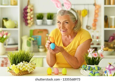 Happy senior woman decorating Easter eggs to holiday