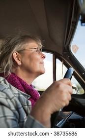 Happy senior woman driving an oldtimer car