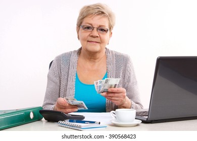 Happy senior woman, an elderly pensioner counting currency money for utility bills at her home, concept of financial security in old age