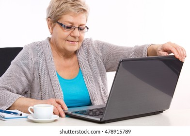 Happy senior woman, an elderly pensioner closing laptop on table at home, shutting down lid of laptop, modern technology in old age