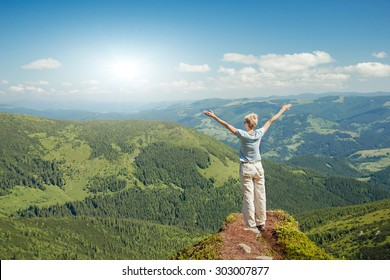 Happy senior woman enjoying the nature in the mountains and looking on sky with raised hands. Freedom concept