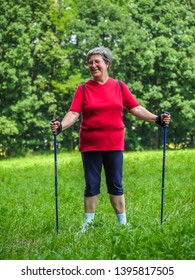 Happy senior woman enjoying Nordic walking in the countryside