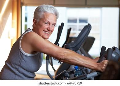 Happy senior woman exercising on bike in gym