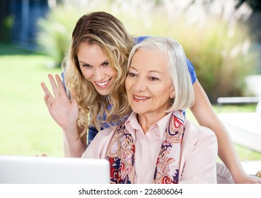 Happy senior woman and granddaughter video chatting on laptop at nursing home porch