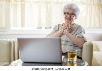 Happy senior woman having video call on laptop at home.