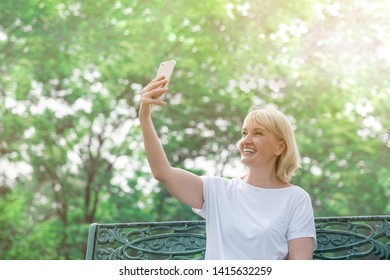 happy senior woman having video call or taking selfie on smartphone in the park, technology and old people concept