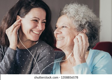 Happy senior woman and her daughter listening to music together. Mother and daughter wearing earphones and sitting on sofa with home interior in background. Happy senior mother and daughter concept.