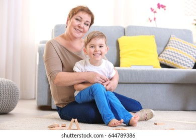 Happy senior woman and her grandson sitting on floor at home