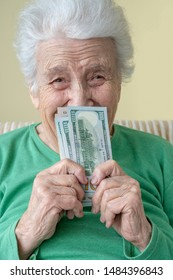 a happy senior woman holding american dollars