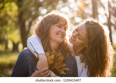 Happy senior woman holding autumn leaves with daughter outside in nature