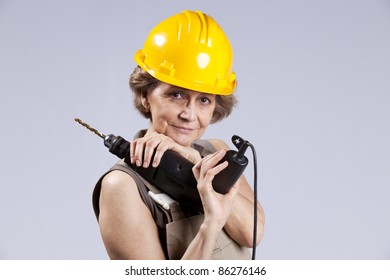 Happy senior woman holding a drill tool (isolated on gray)