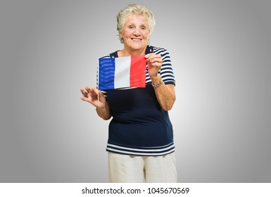 Happy Senior Woman Holding France Flag On Grey Background