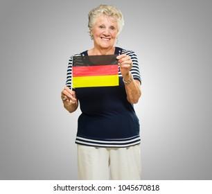 Happy Senior Woman Holding Germany Flag On Grey Background
