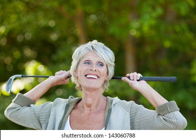 Happy senior woman holding golf club while looking away in park