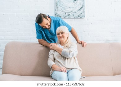 happy senior woman holding hand of young male social worker and smiling at camera