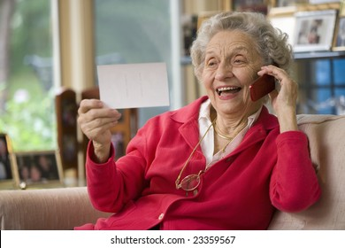 Happy senior woman holding photo and cell phone