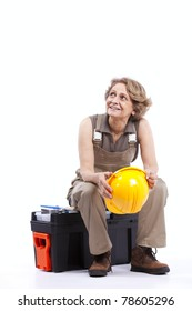 Happy senior woman holding a safety hat sitting in a toolbox (isolated on white)