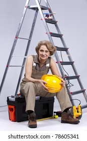 Happy senior woman holding a safety hat sitting in a toolbox