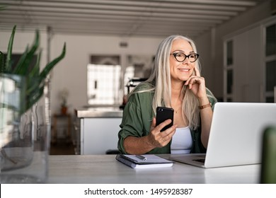 Happy senior woman holding smartphone and laptop daydreaming while looking away. Successful stylish old woman working at home while thinking. Fashionable lady entrepreneur wearing cool eyeglasses.