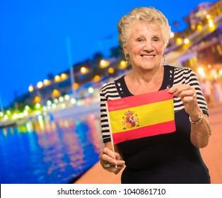 Happy Senior Woman Holding Spain Flag, Outdoors