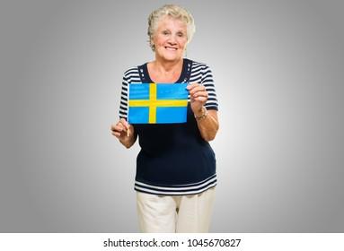 Happy Senior Woman Holding Sweden Flag On Grey Background