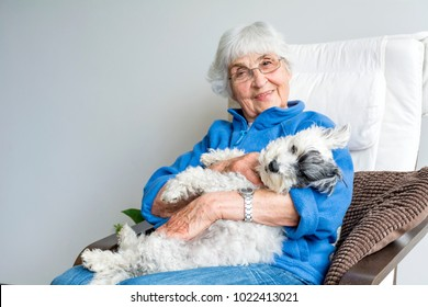 Happy Senior Woman Hugging her Dog at Home
