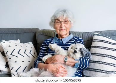 Happy Senior Woman Hugging her Havanese Dog at Home.