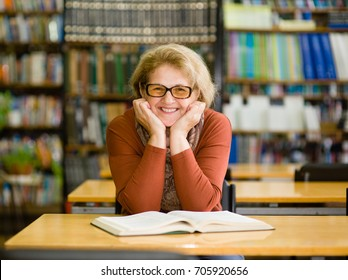 Happy senior woman in library.