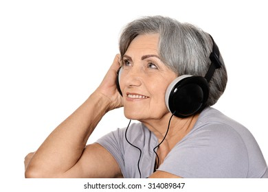 Happy senior woman listen a music in headphones isolated on white background