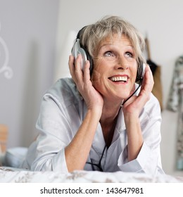 Happy senior woman listening to music through headset while looking up in bed