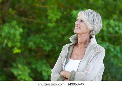 Happy senior woman looking at the beautiful trees