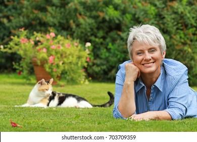 Eine glückliche ältere Frau liegt auf dem Gras im Garten mit einer Katze im Hintergrund