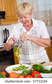 Happy senior woman making a healthy salad in kitchen