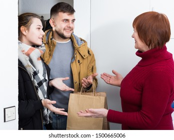 Happy senior woman meeting her adult daughter with husband and welcoming to apartment