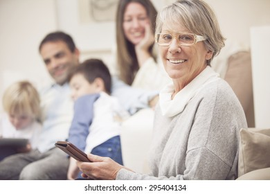 Happy senior woman with mobile phone and family smiling at home