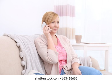 Happy senior woman with phone on couch at home